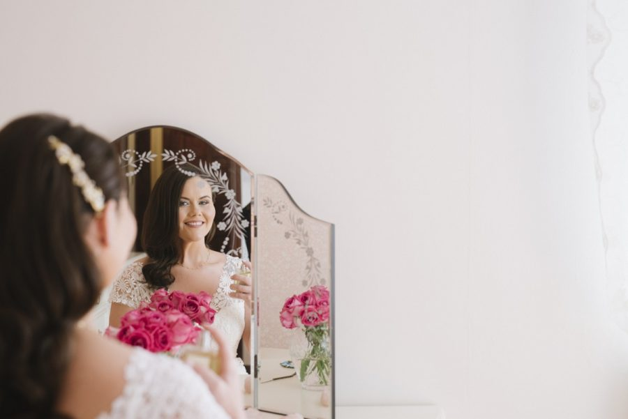 bride on morning of her wedding pink roses